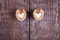 2 половины грецкого ореха в форме сердца лежат на 2 частях  Стоковые Фото