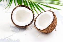 Половины и листья кокоса на белой предпосылке Стоковая Фотография