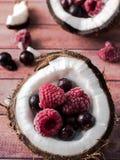 Половины кокоса с замороженными ягодами на темной деревянной предпосылке Стоковое Изображение