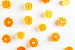 Половины оранжевых и желтых tangerines на белой предпосылке Стоковые Изображения