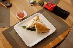 Половины пиццы Calzone на бамбуковом листе в квадратной плите на деревянном столе стоковые фотографии rf