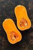 Половины свежей сырцовой тыквы на темной предпосылке Отрезанная овальная форменная тыква Взгляд сверху, плоское положение Концепц стоковое изображение rf
