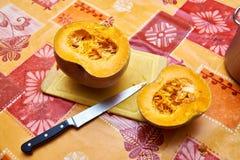 2 половины тыквы на таблице и кухонном ноже Стоковое Изображение