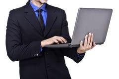 Положение бизнесмена пока печатающ на компьтер-книжке Стоковые Изображения RF