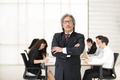 Положение бизнесмена Senoir пока другое младшее sitti бизнесменов стоковые изображения rf