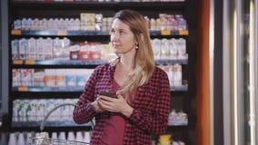 Положение взрослой женщины в супермаркете и использование современного смартфона видеоматериал