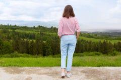 Положение в горе, панорамный вид женщины горной цепи, деревьев E голубое небо, женские нося случайные брюки и стоковые изображения
