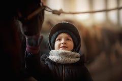 Положение девочка-подростка с лошадью в конюшне стоковая фотография rf