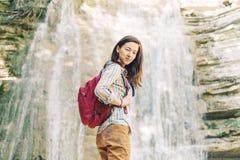 Положение девушки backpacker исследователя на предпосылке водопада стоковые фото