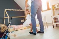 Положение дочери на ногах танцев отца стоковая фотография