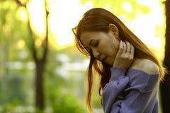 Положение женщины держа ее волосы в парке стоковое фото