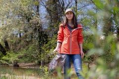 Положение женщины добровольное в древесинах с сумкой отброса Концепция загрязнения окружающей среды Деревья на заднем плане стоковое изображение rf