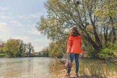 Положение женщины добровольное на речном береге с сумкой отброса Концепция загрязнения окружающей среды Небо, река и деревья внут стоковое изображение rf