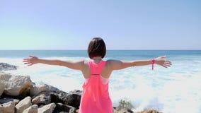Положение женщины молодого брюнета кавказское на скалистом пляже с открытыми оружиями смотря прямо к океану и горизонту ( видеоматериал