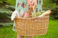 Положение женщины на зеленой траве и удержание корзины пикника с едой, напитками и цветком стоковая фотография