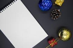 Положение квартиры оформления рождественской елки и тетради пробела на черной предпосылке Модель-макет рождества или Нового Года стоковое фото rf