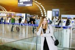 Положение маленькой девочки на зале аэропорта ждать и говорить смартфоном стоковые фотографии rf