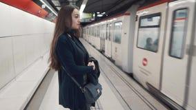 Положение маленькой девочки на платформе и ожидание поезда для того чтобы приехать сток-видео