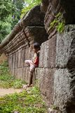 Положение маленькой девочки против старой каменной стены стоковое фото rf