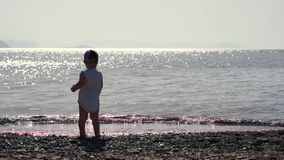 Положение мальчика с его назад к камере бросает камешек в море сток-видео