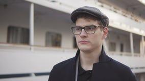 Положение молодого человека около корабля выглядя dval с серьезной стороной акции видеоматериалы
