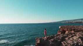 Положение молодой женщины на скалистых скалах в красном платье с руками врозь в воздухе, платье хлопая на ветре Привлекательный ж акции видеоматериалы
