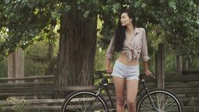 Положение молодой женщины с велосипедом на открытом воздухе видеоматериал