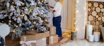 положение около рождественской елки, Новый Год маленькой девочки presents стоковые изображения