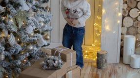 положение около рождественской елки, Новый Год маленькой девочки presents стоковое изображение