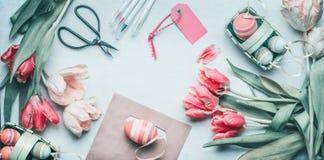 Положение пасхи симпатичного пастельного цвета плоское с яичками, тюльпанами, ножницами и бирками Подготовка приветствию пасхи, в Стоковое фото RF
