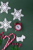 Положение рождества или Нового Года плоское с деревянной диаграммой собаки и снежинок, елей, тросточек конфеты и красных часов Стоковое фото RF