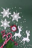 Положение рождества или Нового Года плоское с деревянной диаграммой оленей и снежинок, елей, тросточек конфеты и красных часов Стоковые Фотографии RF