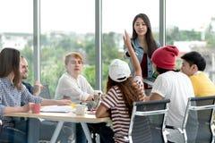 Положение руководителя молодого привлекательного азиатского творческого хипстера женское на говоря современного офиса счастливом  стоковое изображение rf