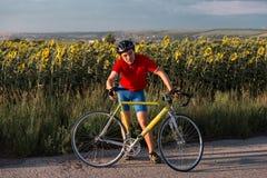 Положение спортсмена рядом с велосипедом Нося спорт зацепляют, шлем и стекла r стоковое фото rf
