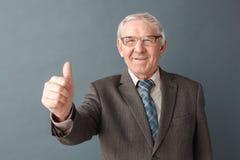 Положение студии стекел учителя старшего человека нося изолированное на сером показывая большом пальце руки вверх по положительно стоковые изображения