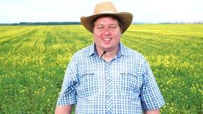 Положение фермера в поле и усмехаться на солнечный день видеоматериал
