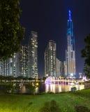 Положение фонтана искусства на ноче с красочными светами мерцающими, за небоскребами Стоковая Фотография RF