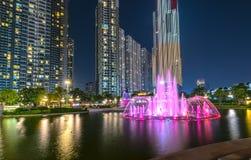 Положение фонтана искусства на ноче с красочными светами мерцающими, за небоскребами Стоковое фото RF