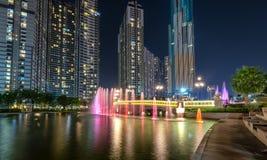 Положение фонтана искусства на ноче с красочными светами мерцающими, за небоскребами Стоковые Фото