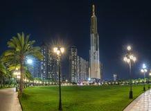 Положение фонтана искусства на ноче с красочными светами мерцающими, за небоскребами Стоковые Изображения