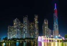 Положение фонтана искусства на ноче с красочными светами мерцающими, за небоскребами Стоковое Изображение RF