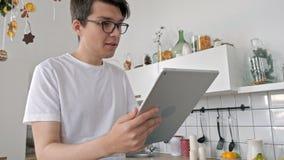 Положение человека в кухне с электронным планшетом Хороший смотря человек дома выпивая кофе используя просторную квартиру цифрово видеоматериал