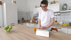 Положение человека в кухне с электронным планшетом Хороший смотря человек дома выпивая кофе используя просторную квартиру цифрово акции видеоматериалы