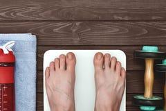 Положение человека в масштабах веса с босыми ногами стоковые фотографии rf