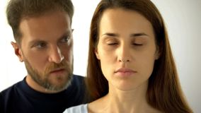 Положение человека за женой, грустной дамой с закрытыми глазами слыша решения супруга стоковое фото