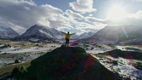 Положение человека на успехе достижения горной цепи зимы Snowy пика утеса протягивало красоту природы эпопеи счастья оружий