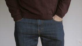 Положение человека перед белой стеной рассматривает содержание их карманов брюк, хлопая ее руки в сток-видео