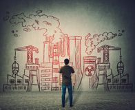 Положение человека перед бетонной стеной с различной нарисованной фабрикой Ядерные установки, токсический дым грязной концепции и стоковое изображение