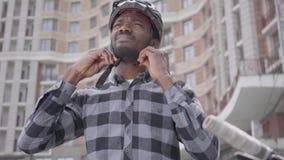 Положение человека портрета confidient красивое Афро-американское с велосипедом перед высоким строя небоскребом нося a видеоматериал