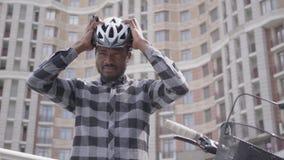 Положение человека портрета confidient красивое Афро-американское с велосипедом перед высоким строя небоскребом кладет велосипед видеоматериал